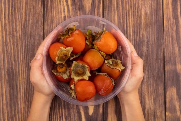 木製の表面に熟した柔らかくてジューシーな柿の透明なプラスチック製のボウルを保持している女性の手の上面図