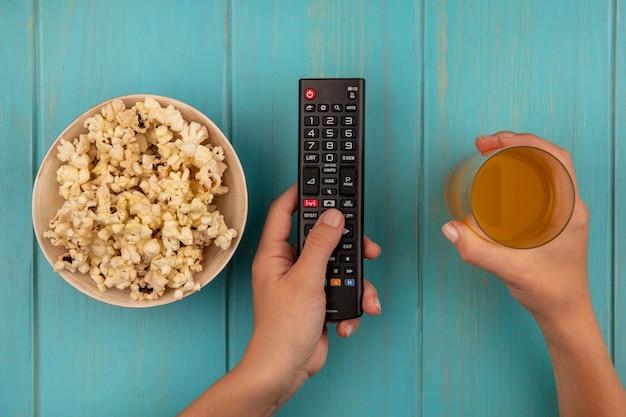 青い木製のテーブルにおいしいポップコーンのボウルとオレンジジュースのガラスを保持している女性の手の上面図