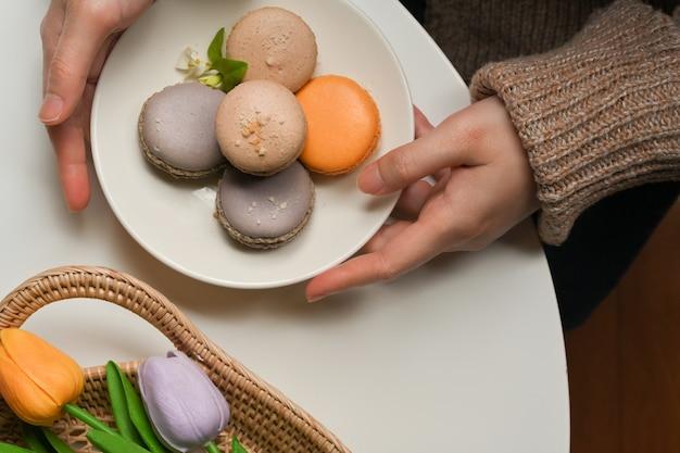 チューリップとコーヒーテーブルに置くためにフランスのカラフルなマカロンのプレートを保持している女性の手の上面図