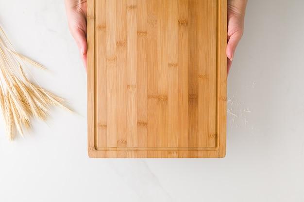 텍스트에 대 한 공간을 가진 밀가루와 밀가루와 대리석 테이블에 나무 보드를 들고 여성 손의 상위 뷰
