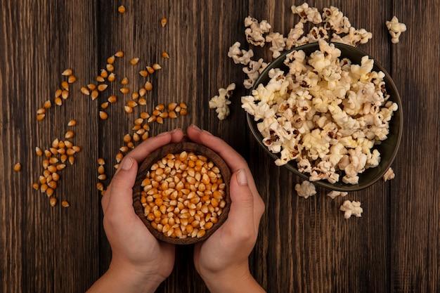 木製のテーブルの上のボウルにポップコーンとトウモロコシの穀粒の木製のボウルを保持している女性の手の上面図