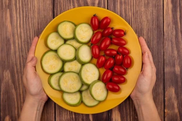 トマトやズッキーニなどの新鮮な野菜の黄色いプレートを木の表面に持っている女性の手の上面図