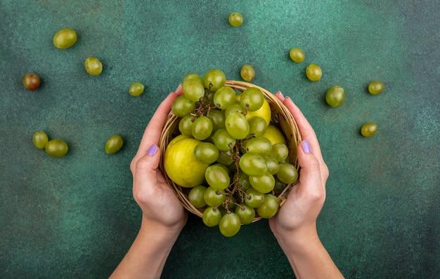 緑の背景にブドウとブドウの果実とプルートとして果物のバスケットを保持している女性の手の上から見る