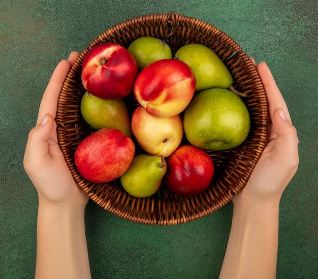緑の背景に梨桃リンゴとして果物のバスケットを保持している女性の手の上から見る