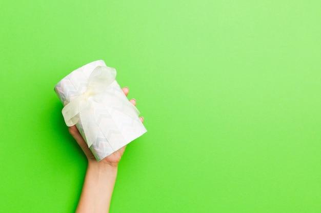 손바닥에 크리스마스 또는 다른 휴일 수제 선물 상자 패키지를 들고 여성 손의 상위 뷰, 복사 공간이 평평한 평신도 테이블 표면