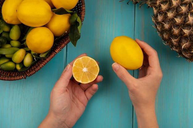 青い木製の壁のバケツにキンカンやレモンなどの果物と新鮮なレモンを保持している女性の手の上面図