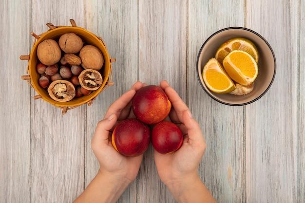 灰色の木製の背景の上のボウルにみかんとバケツにナッツと新鮮な赤桃を保持している女性の手の上面図