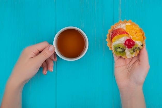 青い木製の背景にフルーツタルトとお茶のカップを保持している女性の手の上面図