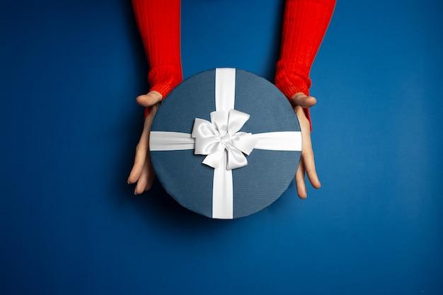 파란색에 흰색 나비와 선물 상자를 들고 여성 손의 최고 볼 수 있습니다. 무성한 용암 색 스웨터를 입고.