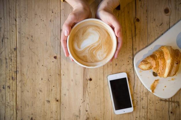 木製のテーブルの上のスマートフォンで熱いコーヒーを保持している女性の手の上面図
