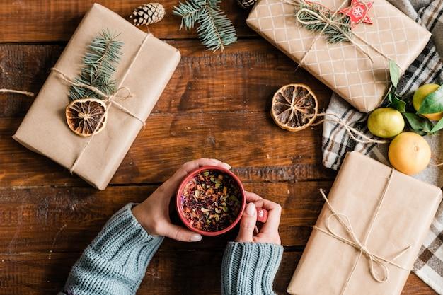 Вид сверху на женские руки, держащие кружку с горячим травяным напитком среди подарочных коробок, украшений и клементинов