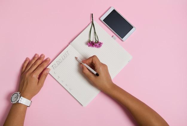 연필을 들고 공책에 글을 쓰고 할 일 목록을 확인하는 여성 손의 맨 위. 휴대 전화와 분홍색 꽃은 복사 공간이 있는 분홍색 배경에 놓여 있습니다. 비즈니스, 계획 및 시간 관리 개념