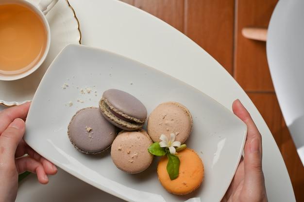 ティーカップとコーヒーテーブルに置くためにフランスのマカロンのプレートを保持している女性の手の上面図