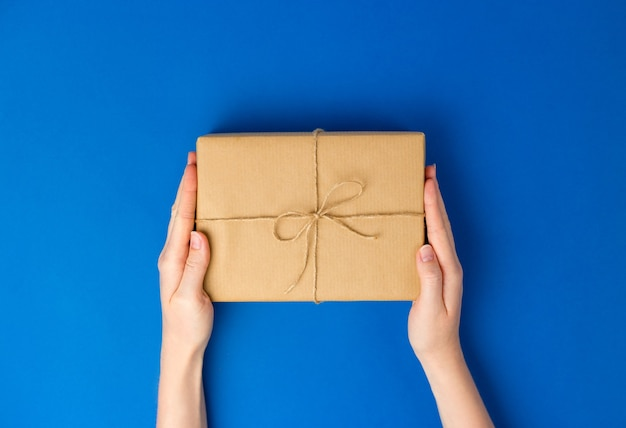 青い背景にプレゼントボックスパッケージを保持している女性の手の上面図。ゼロウェイストショッピングコンセプト。フラットレイバナー、上面図、持続可能なライフスタイル。