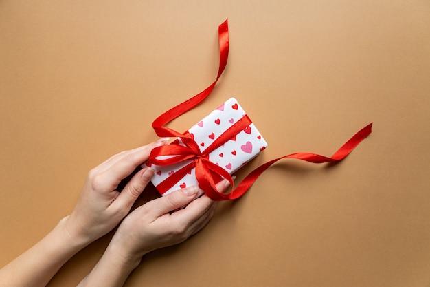 フラットレイの背景の上にプレゼントボックスパッケージを保持している女性の手の上面図。