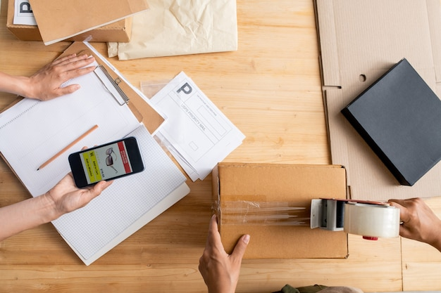 Вид сверху на женские руки, держащие смартфон со страницей интернет-магазина над документом, в то время как ее коллега запечатывает упакованный заказ клиента