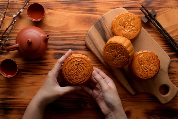 素朴なテーブルにお茶セットと月餅の伝統的な月餅を保持している女性の手の上から見る。月餅の漢字は英語で「五穀とローストポーク」を表す