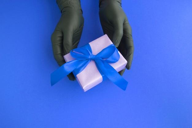파란색 배경에 선물 상자와 검은 장갑에 여성 손의 상위 뷰