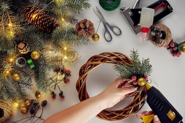 女性の手の上面図はクリスマスリースを作ります。白いテーブルの上に詰められた贈り物と巻物、トウヒの枝と道具。クリスマスや年末年始の準備