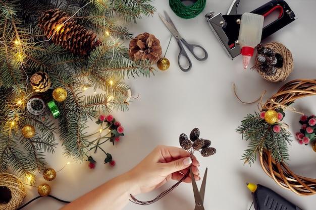 女性の手の上面図はクリスマスリースを作ります。白いテーブルの上に詰められた贈り物と巻物、トウヒの枝と道具。