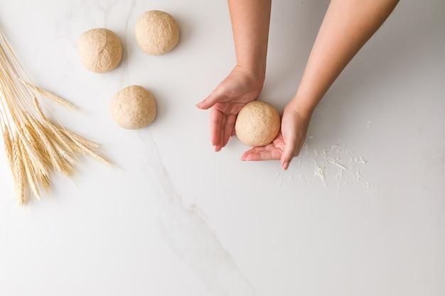 텍스트를위한 공간 3 성형 빵 반죽, 밀, 밀가루와 대리석 테이블에 빵 반죽을 성형 여성 손의 상위 뷰