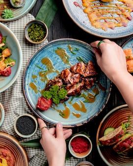 Вид сверху женских рук положить тарелку с жареной курицей с помидорами гриль свежей зеленью и соусом на столе
