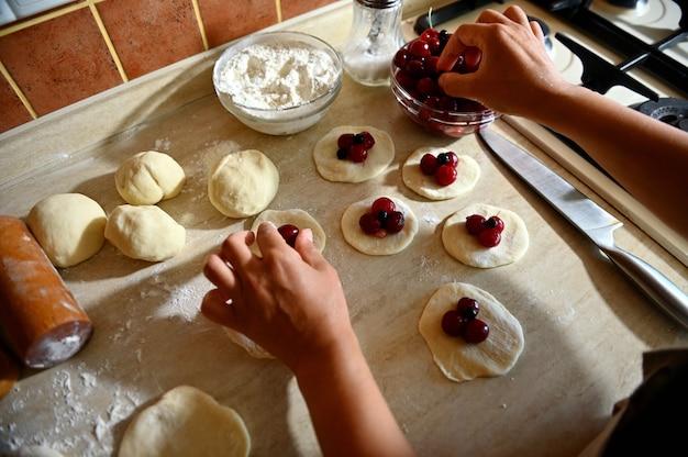 ウクライナの伝統的な餃子を埋めて、生地の丸い形にチェリーベリーを置く女性の手の上面図。キッチンで餃子を段階的に調理するプロセス