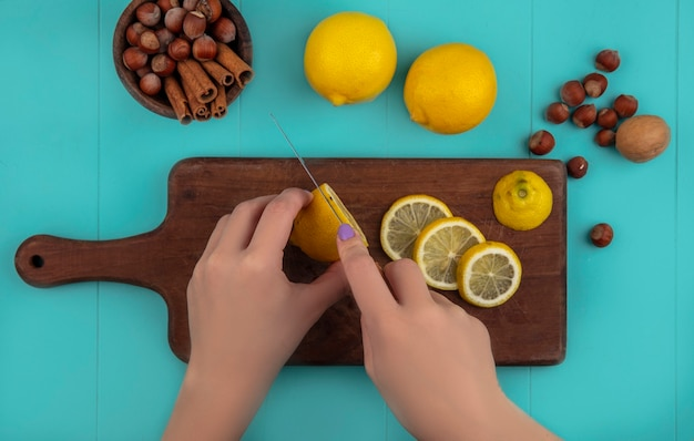 Вид сверху на женские руки, нарезающие лимон ножом на разделочной доске и миску с корицей и орехами с лимонами на синем фоне