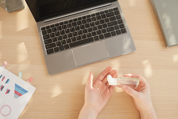 Вид сверху женских рук, использующих дезинфицирующее средство на рабочем месте, освещенном солнечным светом