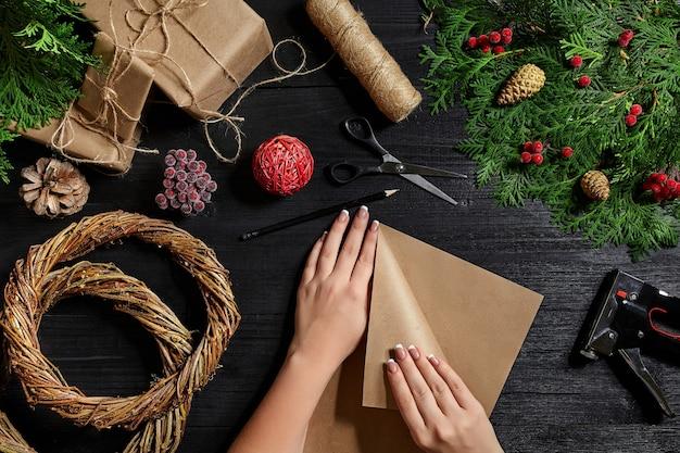 Вид сверху на женские руки, обертывающие новогодний подарок, упакованные подарки и свитки еловых веток и инструментов на ...