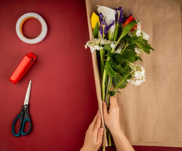 咲くガマズミオランダカイウユリと暗い紫色のアイリスの花の花束をクラフトペーパーとはさみ、ホッチキス、濃い赤のテーブルに粘着テープのロールで包む女性の手の平面図