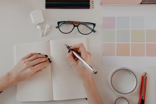 白いテーブルの上の事務用品の日記に何かを書いている女性の手の上面図。