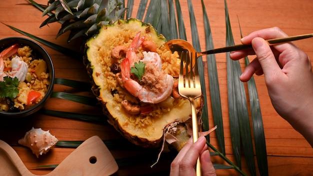 カットパイナップルボウルでパイナップルチャーハン(カオパッドサッパロッド)を食べるためにカトラリーを持っている女性の上面図