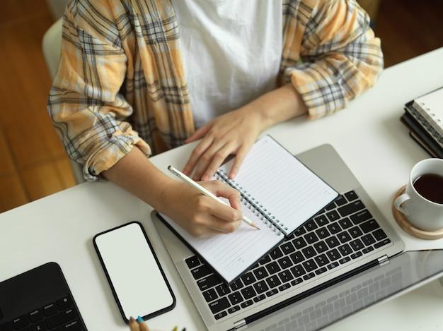 Вид сверху женщины в куртке скотта, почеркнувшей пустой блокнот и работающей со смартфоном и ноутбуком на обтравочном контуре стола