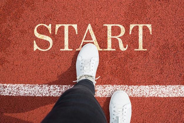 白いスニーカーの女性の脚の上面図は、最初の一歩を踏み出します。言葉はトレッドミルで始まります。新年のコンセプト。