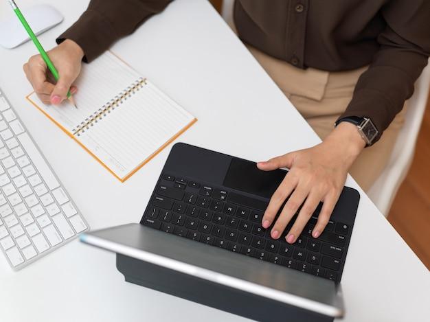 Вид сверху офисного работника, работающего с цифровым планшетом и канцелярскими принадлежностями на компьютерном столе