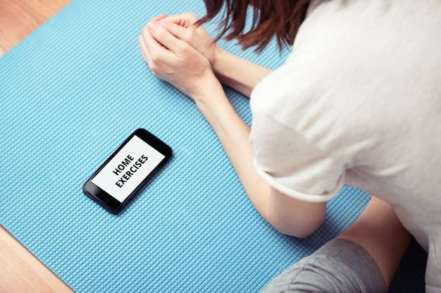 스포츠 매트에 앉아서 스마트폰을 보고 있는 여성의 상위 뷰. 집에서 운동. 휴대폰 화면에 비문입니다. 스포츠와 건강한 라이프 스타일. 격리 기간. 홈 운동 개념입니다.