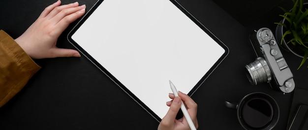 暗いモダンなコンセプトのワークスペースでタブレットに取り組んでいる女性写真家の平面図