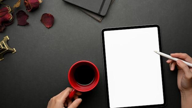 Вид сверху женщины, работающей с цифровым планшетом, включая экран и держащую чашку кофе на черном творческом рабочем пространстве