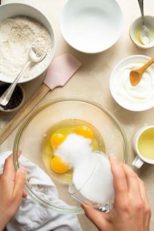 ガラスのボウルの卵の上に砂糖を注ぐ女性の手の上面図。ステップバイステップのレシピ。 Premium写真