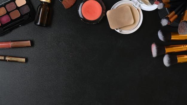 口紅、アイパレット、フェイスパウダー、ブラシ、暗い背景のコピースペースを備えたフェミニンなデスクの上面図。