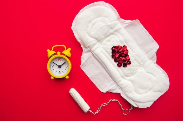 빨간색 반짝이와 노란색 알람 시계가있는 여성용 패드와면 탐폰의 상위 뷰.