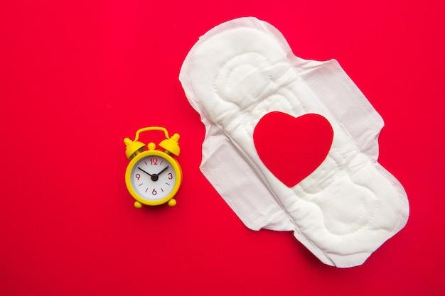 빨간색에 종이 심장과 노란색 알람 시계와 여성 패드의 상위 뷰