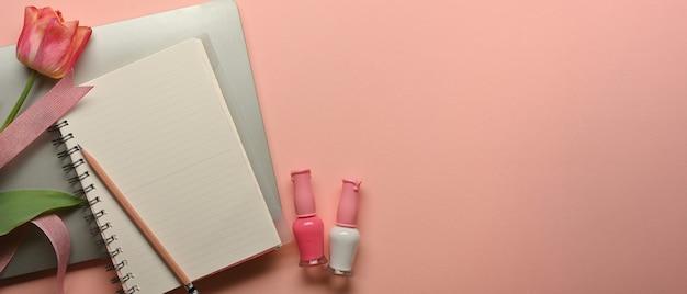 ノートブック、マニキュア、花、ホームオフィスルームのコピースペースとフェミニンなワークスペースの上面図