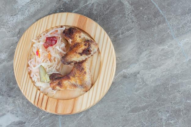 나무 접시에 발효된 양배추의 상위 뷰입니다. 구운 치킨과 함께.