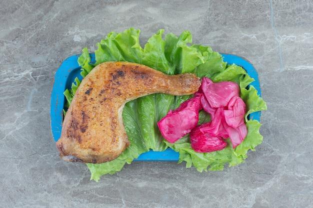 Вид сверху ферментированной капусты с жареной куриной ножкой с листьями салата.