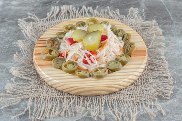 Вид сверху ферментированной капусты с кусочками рассола на деревянной тарелке.