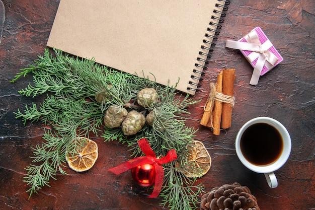 전나무 가지와 펜 계피 라임이 있는 닫힌 나선형 노트북의 꼭대기 전망은 어두운 배경에 홍차 한 잔을 선물합니다