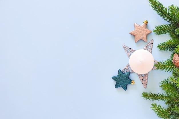 Вид сверху еловых веток, белой свечи, звезд и сосновых шишек на пастельно-синем столе