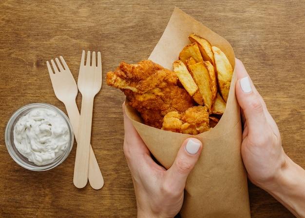 Вид сверху на рыбу с жареным картофелем в бумажной упаковке, которую держит женщина